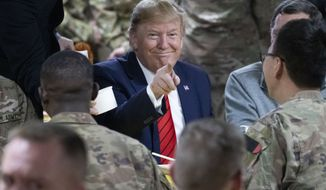 President Donald Trump points while eating during a surprise Thanksgiving Day visit to the troops, Thursday, Nov. 28, 2019, at Bagram Air Field, Afghanistan. (AP Photo/Alex Brandon)