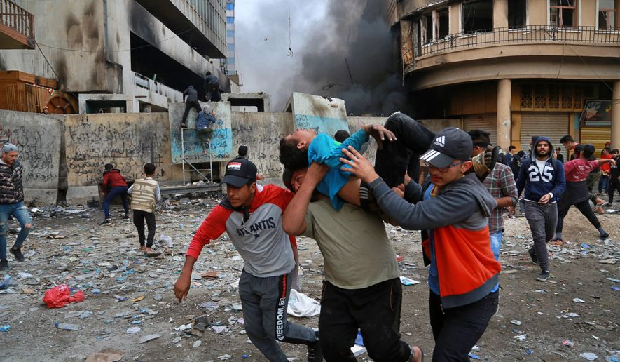 A wounded protester is carried to receive first aid during clashes with security forces on Rasheed Street in Baghdad, Iraq, Thursday, Nov. 28, 2019. Anti-government protests have gripped Iraq since Oct. 1, when thousands took to the streets in Baghdad and the predominantly Shiite south. The largely leaderless movement is accusing the government of being hopelessly corrupt, and also decries Iran's growing influence in Iraqi state affairs. (AP Photo/Khalid Mohammed)