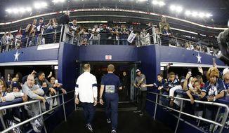 Dallas Cowboys head coach Jason Garrett, center, walks off the field past fans after their NFL football game against the Buffalo Bills in Arlington, Texas, Thursday, Nov. 28, 2019. (AP Photo/Ron Jenkins)