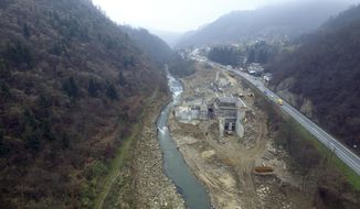 This aerial photo taken Wednesday, Nov. 27, 2019, shows small hydropower plant under construction on Lasva river, near village of Merdani, Bosnia. Environmental groups and activists have warned that unspoiled rivers in the Balkans are in danger from small hydropower plants that have been sprouting throughout the region. (AP Photo/Eldar Emric)
