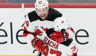 New Jersey Devils' Miles Wood (44) celebrates with teammate Pavel Zacha after scoring against the Montreal Canadiens during second-period NHL hockey game action in Montreal, Thursday, Nov. 28, 2019. (Graham Hughes/The Canadian Press via AP)