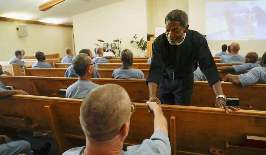 In this Aug. 20, 2019, photo, Deacon Joe Bakker greets one of the Jefferson Correctional Institution inmates who participates in the parables class he teaches at the prison in Monticello, Fla. (Tori Schneider/Tallahassee Democrat via AP) **FiLE**