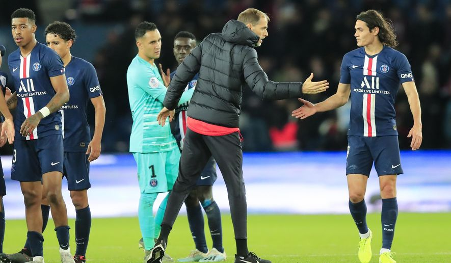 PSG coach Thomas Tuchel, second right, celebrates with teammate Edinson Cavani at the end of the French League One soccer match between Paris Saint-Germain and Lille at the Parc des Princes stadium in Paris, Friday, Nov. 22, 2019. PSG won 2-0. (AP Photo/Michel Euler)