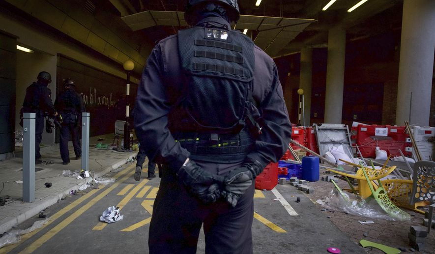 A policeman from Explosive Ordnance Disposal (EOD) unit looks at the debris at the Hong Kong Polytechnic University campus in Hong Kong, Thursday, Nov. 28, 2019. Police safety teams Thursday began clearing the university that was a flashpoint for clashes with protesters, and an officer said any holdouts still hiding inside would not be immediately arrested. (AP Photo/Ng Han Guan)