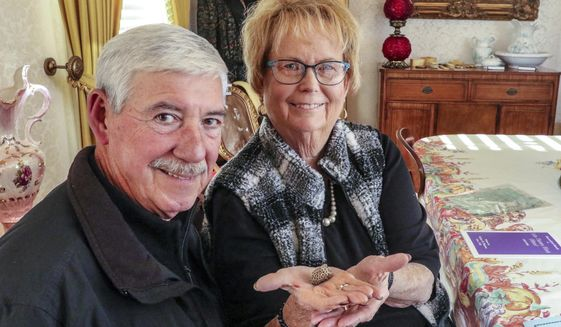 In this Wednesday, Nov. 20, 2019 photo, Pat Gibson, left, poses with Charlotte Whittaker as she hold a colonial-period madstone at the Whitesville Historical Society in Whitesville, Ky. Whittaker's ancestors brought the stone from England to America in the 1600s. The madstone, a piece of fossilized coral, was once thought to possess healing powers. (Greg Eans/The Messenger-Inquirer via AP)