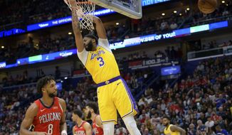 Los Angeles Lakers forward Anthony Davis (3) dunks next New Orleans Pelicans center Jahlil Okafor (8) during the first half of an NBA basketball game in New Orleans, Wednesday, Nov. 27, 2019. (AP Photo/Matthew Hinton)