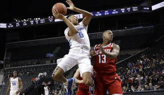 Memphis' Boogie Ellis (5) shoots over North Carolina State's C.J. Bryce (13) during the first half of an NCAA college basketball game in the Barclays Classic, Thursday, Nov. 28, 2019, in New York. (AP Photo/Frank Franklin II)