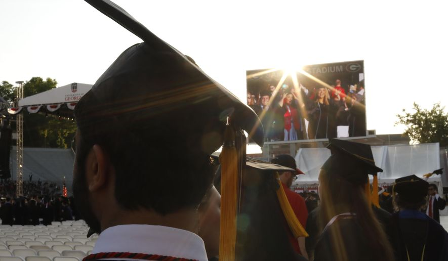 FILE - In this May 10, 2019, file photo graduates enter Sanford Stadium during the University of Georgia's Spring commencement in Athens, Ga. The first student loan bills are arriving for the Class of 2019. If the grads are able to stick to the standard plan, they'll make payments every month for the next 10 years and be done with it. (Joshua L. Jones/The Athens Banner-Herald via AP, File)