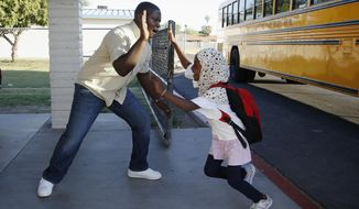 Samuel Lavi, left, a Congolese native who is a teaching assistant and family engagement liaison, greets first grader Kediga Ahmed as she arrives at the Valencia Newcomer School attend class Thursday, Oct. 17, 2019, in Phoenix. Children from around the world are learning the English skills and American classroom customs they need to succeed at so-called newcomer schools. Valencia Newcomer School in Phoenix is among a handful of such public schools in the United States dedicated exclusively to helping some of the thousands of children who arrive in the country annually.   (AP Photo/Ross D. Franklin)
