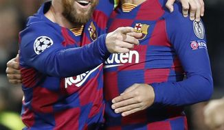 Barcelona's Lionel Messi, left, celebrates after scoring his side's second goal with Antoine Griezmann during a Champions League soccer match Group F between Barcelona and Dortmund at the Camp Nou stadium in Barcelona, Spain, Wednesday, Nov. 27, 2019. (AP Photo/Joan Monfort)