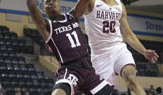Texas A&M guard Wendell Mitchell (11) is fouled by Harvard guard Justin Bassey (20) while going up for a shot during the second half of an NCAA college basketball tournament game Thursday, Nov. 28, 2019, in Lake Buena Vista, Fla. (AP Photo/Phelan M. Ebenhack)