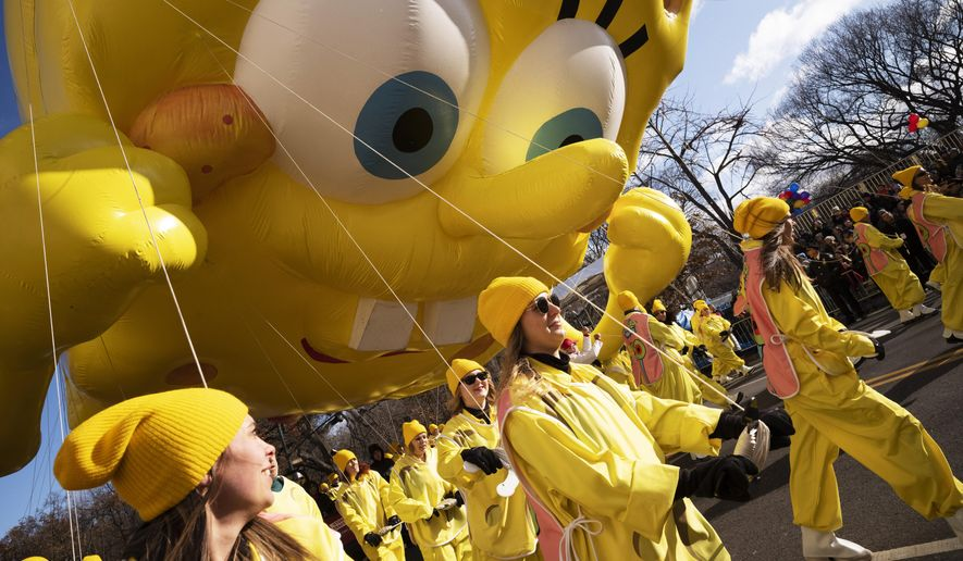 Balloon handlers hold SpongeBob Square Pants balloon close to the ground as strong winds affect the Macy's Thanksgiving Day Parade, Thursday, Nov. 28, 2019, in New York. (AP Photo/Mark Lennihan)