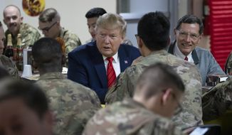 President Donald Trump, center, smiles as he eats dinner accompanied by Sen. John Barrasso, R-Wyo., right, during a surprise Thanksgiving Day visit to the troops, Thursday, Nov. 28, 2019, at Bagram Air Field, Afghanistan. (AP Photo/Alex Brandon)