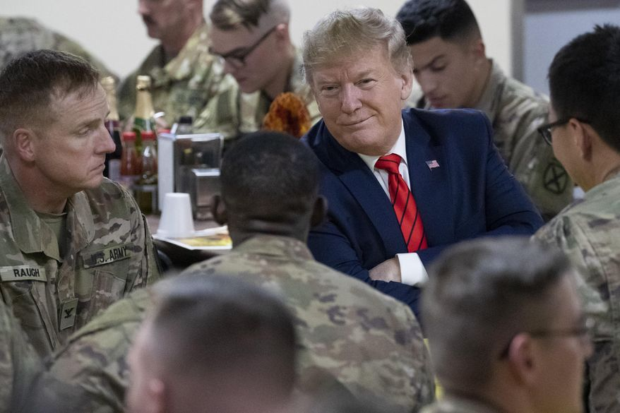 President Donald Trump smiles while sitting with the troops during a surprise Thanksgiving Day visit to the troops, Thursday, Nov. 28, 2019, at Bagram Air Field, Afghanistan. (AP Photo/Alex Brandon)
