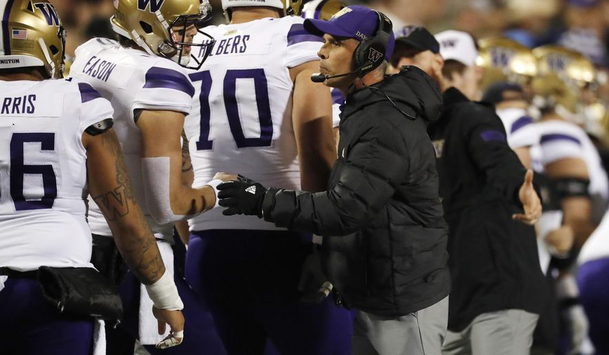 Washington quarterback Jacob Eason, left, confers with coach Chris Petersen during the first half of the team's NCAA college football game against Colorado on Saturday, Nov. 23, 2019, in Boulder, Colo. (AP Photo/David Zalubowski)