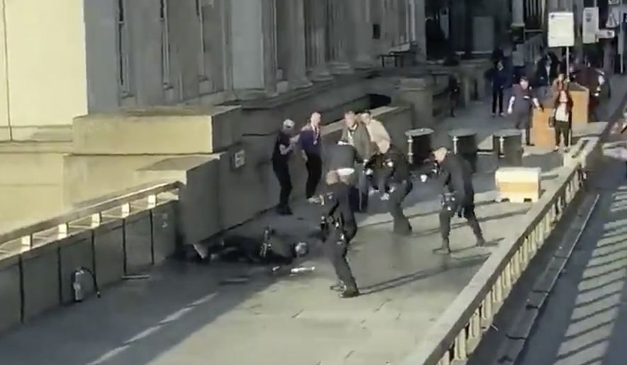 In this grab taken from video made available by @HLOBlog, a man is surrounded by police after an incident on London Bridge, in London, Friday, Nov. 29, 2019. A man wearing a fake explosive vest stabbed several people before being tackled by members of the public and then shot dead by armed officers on London Bridge, police and the citys mayor say. Police say they are treating it as a terrorist attack. (@HLOBlog via AP)