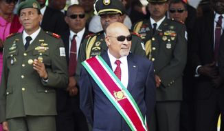 """In this Aug. 12, 2015, file photo, Suriname President Desire """"Desi"""" Delano Bouterse observes a military parade, after being sworn in for his second term, in Paramaribo, Suriname. A Suriname court on Friday, Nov. 29, 2019, convicted Bouterse in the 1982 killings of 15 political opponents and sentenced him to 20 years in prison. (AP Photo/Ertugrul Kilic, File)"""