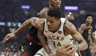 Milwaukee Bucks' Giannis Antetokounmpo (34) drives past Cleveland Cavaliers' Alfonzo McKinnie, top, in the first half of an NBA basketball game, Friday, Nov. 29, 2019, in Cleveland. (AP Photo/Tony Dejak)