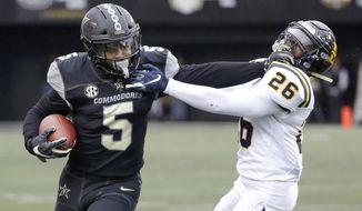 Vanderbilt running back Ke'Shawn Vaughn (5) tries to get past ETSU defensive back Artevius Smith (26) in the first half of an NCAA college football game Saturday, Nov. 23, 2019, in Nashville, Tenn. (AP Photo/Mark Humphrey)