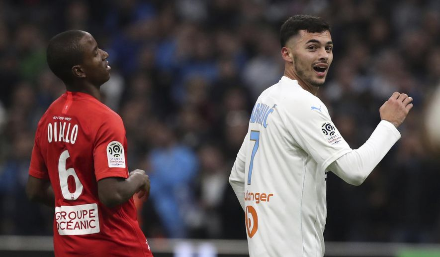 Marseille's Nemanja Radonjic celebrates ahead of Brest's Ibrahima Diallo after scoring his side's second goal during the French League One soccer match between Marseille and Brest at the Velodrome stadium in Marseille, southern France, Friday, Nov. 29, 2019. (AP Photo/Daniel Cole)