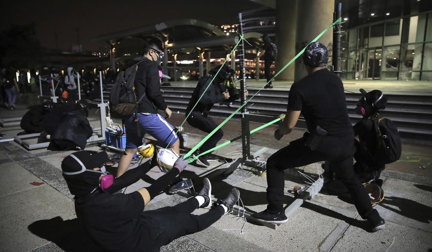 """In this Thursday, Nov. 14, 2019, file photo, protestors practice using a homemade slingshot at Hong Kong Polytechnic University in Hong Kong. Hong Kong police warned protesters on Thursday that they were moving """"one step closer to terrorism"""" by sinking the city into chaos, as riot squads skirmished with militant students at major universities. (AP Photo/Kin Cheung, File)"""