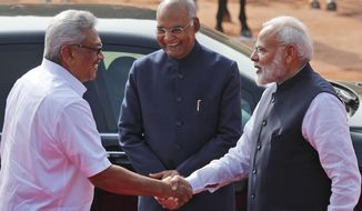 Indian Prime Minister Narendra Modi, right, shakes hand with Sri Lankan President Gotabaya Rajapaksa, as Indian President Ram Nath Kovind stands beside them, during a ceremonial reception for Rajapaksa at the Presidential Palace in New Delhi, India, Friday, Nov. 29, 2019. Rajapaksa is on a three-day official visit to the country. (AP Photo/Manish Swarup)