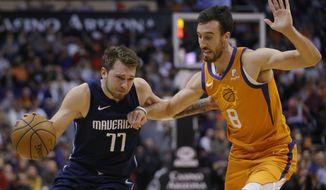 Dallas Mavericks forward Luka Doncic drives on Phoenix Suns forward Frank Kaminsky (8) during the first half of an NBA basketball game Friday, Nov. 29, 2019, in Phoenix. (AP Photo/Rick Scuteri)