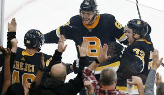 Boston Bruins' David Krejci (46) celebrates his winning goal with David Pastrnak (88) and Charlie McAvoy (73) in overtime during an NHL hockey game against the New York Rangers in Boston, Friday, Nov. 29, 2019. (AP Photo/Michael Dwyer)