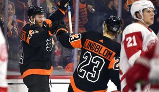 Philadelphia Flyers' Sean Couturier, left, celebrates with Oskar Lindblom (23) after Couturier scored a goal during the second period of an NHL hockey game against the Detroit Red Wings, Friday, Nov. 29, 2019, in Philadelphia. (AP Photo/Derik Hamilton)