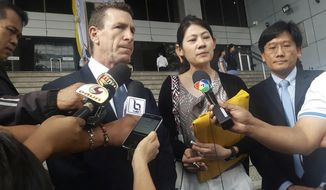 Gerald Margolis, center left, branch manager of Philip Morris in Thailand, talks to reporters at Criminal Court in Bangkok, Thailand, Friday, Nov. 29, 2019. The court has found the local unit of tobacco giant Philip Morris guilty of evading taxes by under-declaring the value of cigarettes it imported from the Philippines, and ordered the company to pay a fine of 1.2 billion baht ($39.7 million). (AP Photo)