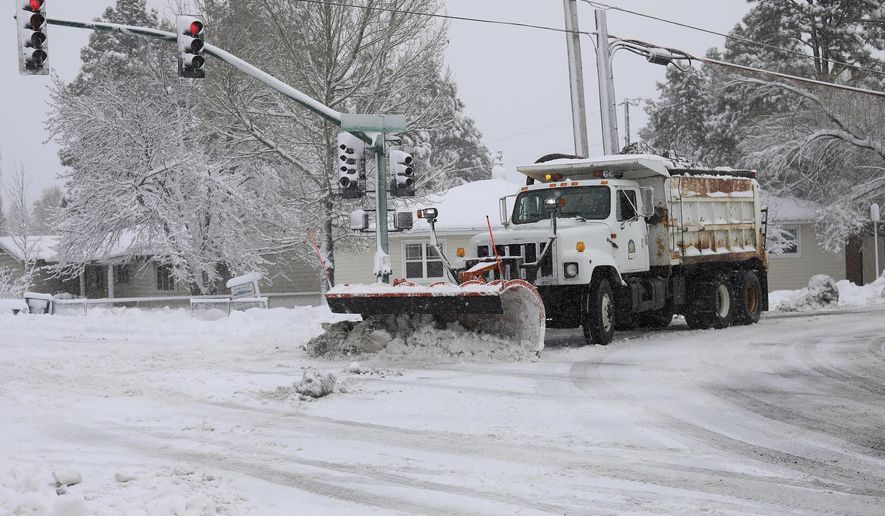 A city snowplow helps clear roads north of downtown Flagstaff, Ariz., Friday, Nov. 29, 2019. A powerful storm making its way east from California is threatening major disruptions during the year's busiest travel weekend, as forecasters warned that intensifying snow and ice could thwart millions across the country hoping to get home after Thanksgiving. The storm has already killed at least one person and shut down highways in the western U.S., stranding drivers in California and prompting authorities in Arizona to plead with travelers to wait out the weather before attempting to travel. (Cody Bashore/Arizona Daily Sun via AP)