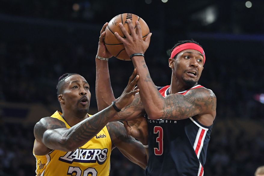 Washington Wizards guard Bradley Beal, right, tries to pass the ball as Los Angeles Lakers center Dwight Howard reaches for it during the second half of an NBA basketball game Friday, Nov. 29, 2019, in Los Angeles. The Lakers won 125-103. (AP Photo/Mark J. Terrill) ** FILE **