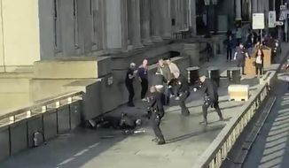 In this grab taken from video made available by @HLOBlog, a man is surrounded by police after an incident on London Bridge, in London, Friday, Nov. 29, 2019. A man wearing a fake explosive vest stabbed several people before being tackled by members of the public and then shot dead by armed officers on London Bridge, police and the city's mayor say. Police say they are treating it as a terrorist attack. (@HLOBlog via AP)
