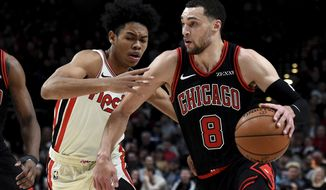 Chicago Bulls guard Zach LaVine, right, drives to the basket on Portland Trail Blazers guard Anfernee Simons during the first quarter of an NBA basketball game in Portland, Ore., Friday, Nov. 29, 2019. (AP Photo/Steve Dykes)