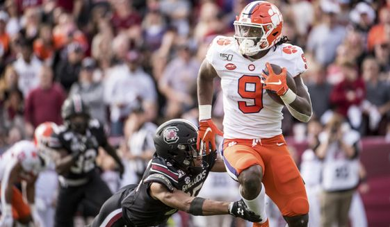 Clemson running back Travis Etienne (9) carries the ball against South Carolina's A.J. Turner during the first half of an NCAA college football game Saturday, Nov. 30, 2019, in Columbia, S.C. (AP Photo/Sean Rayford)
