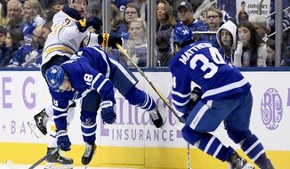 Buffalo Sabres center Jack Eichel (9) checks Toronto Maple Leafs left wing Andreas Johnsson (18) as Maple Leafs' Auston Matthews (34) watches during third-period NHL hockey action in Toronto, Saturday, Nov. 30, 2019. (Nathan Denette/The Canadian Press via AP)
