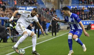 Real Madrid's Karim Benzema, left, duels for the ball with Alaves' Ximo Navarro during the Spanish La Liga soccer match between Real Madrid and Alaves at Mendizorroza stadium, in Vitoria, northern Spain, Saturday, Nov. 30, 2019. (AP Photo/Alvaro Barrientos)