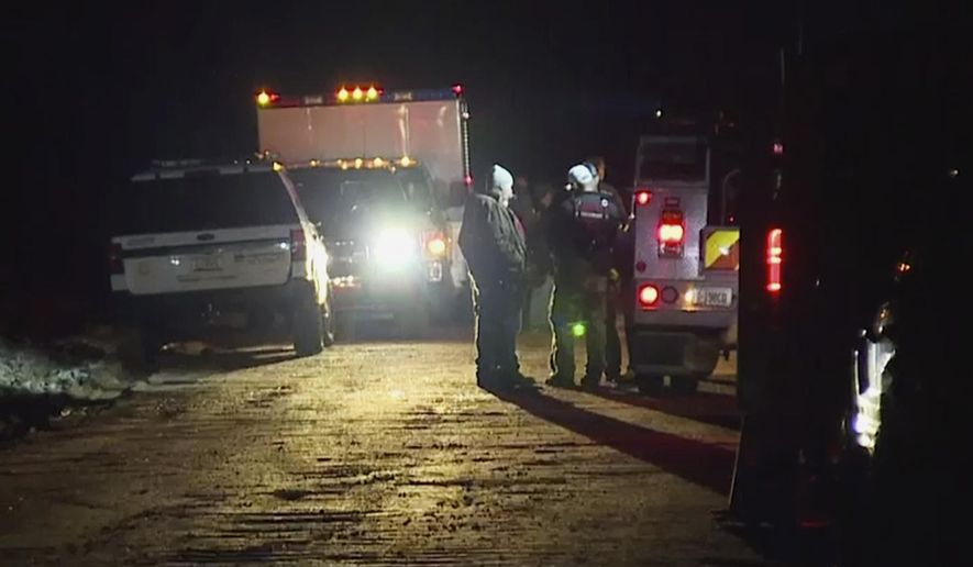 In this image made from Friday, Nov. 29, 2019, video provided by KNXV-TV, emergency personnel and law enforcement members gather while searching people including children after a vehicle was swept away while attempting to cross a runoff-swollen creek in Tonto Basin, northeast of Phoenix. Authorities said Saturday they have found the bodies of a few young children. (KNXV-TV via AP)