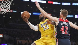 Los Angeles Lakers forward LeBron James, left, shoots as Washington Wizards forward Davis Bertans defends during the first half of an NBA basketball game Friday, Nov. 29, 2019, in Los Angeles. (AP Photo/Mark J. Terrill)