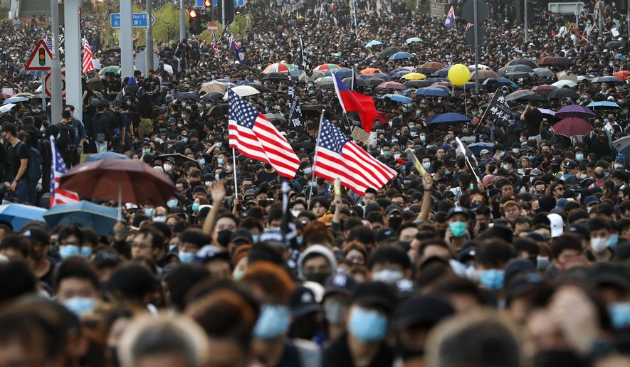 Pro-democracy protesters flood a street during a rally in Hong Kong, Sunday, Dec. 1, 2019. A huge crowd took to the streets of Hong Kong on Sunday, some driven back by tear gas, to demand more democracy and an investigation into the use of force to crack down on the six-month-long anti-government demonstrations. (AP Photo/Vincent Thian)