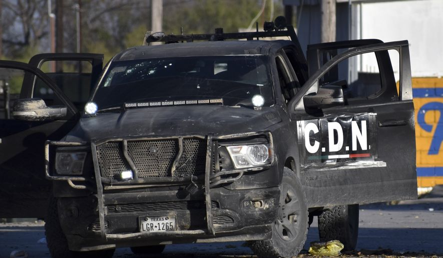 A damaged pick up marked with the initials C.D.N., that in Spanish stand for Cartel of the Northeast, is on the streets after a gun battle between Mexican security forces and suspected cartel gunmen, in Villa Union, Mexico, Saturday, Nov. 30, 2019. At least 14 people were killed, four of them police officers, after an armed group in a convoy of trucks stormed the town, in Coahuila state, prompting security forces to intervene, state Gov. Miguel Riquelme Solis said. (AP Photo/Gerardo Sanchez)