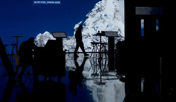 A worker walks on a stand at the COP25 Climate summit a day before the start in Madrid, Spain, Sunday, Dec. 1, 2019. This year's international talks on tackling climate change were meant to be a walk in the park compared to previous instalments. But with scientists issuing dire warnings about the pace of global warming and the need to urgently cut greenhouse gas emissions, officials are under pressure to finalize the rules of the 2015 Paris accord and send a signal to anxious voters. (AP Photo/Paul White)