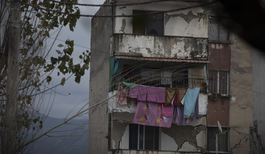 In this Wednesday, Nov. 27, 2019 photo, laundry hangs on a line from a damaged building in Thumane, western Albania following a deadly earthquake. A handbag dangles from a coat-hanger, gleaming saucepans sit stacked in a kitchen cabinet, sheets and duvets lie neatly folded in a bedroom cupboard. All scenes of ordinary domesticity, except for one detail: the rest of the homes these ordinary items were part of have vanished, crumpling in the devastating force of an earthquake that struck Albania earlier this week.(AP Photo/Petros Giannakouris)