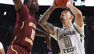 Georgia Tech guard Michael Devoe (0) draws a foul for a three-point play while shooting over Bethune-Cookman defender Cletrell Pope in the final seconds for a victory in an NCAA college basketball game Sunday, Dec. 1, 2019, in Atlanta. (Curtis Compton/Atlanta Journal-Constitution via AP)