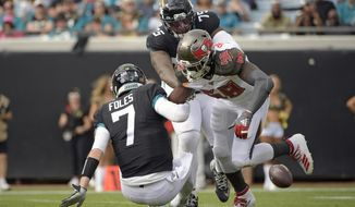 Jacksonville Jaguars quarterback Nick Foles (7) fumbles the ball as he is hit by Tampa Bay Buccaneers linebacker Shaquil Barrett (58) during the first half of an NFL football game, Sunday, Dec. 1, 2019, in Jacksonville, Fla. (AP Photo/Phelan M. Ebenhack)