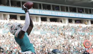 Miami Dolphins wide receiver DeVante Parker (11) catches a pass for a touchdown as Philadelphia Eagles cornerback Jalen Mills (31) defends, during the second half at an NFL football game, Sunday, Dec. 1, 2019, in Miami Gardens, Fla. (AP Photo/Lynne Sladky)