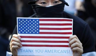 A protester holds a placard carrying an American flag during a rally in Hong Kong, Sunday, Dec. 1, 2019. Hong Kong protesters carrying American flags and banners appealing to President Donald Trump are rallying in the semi-autonomous Chinese territory. (AP Photo/Vincent Thian) **FILE**