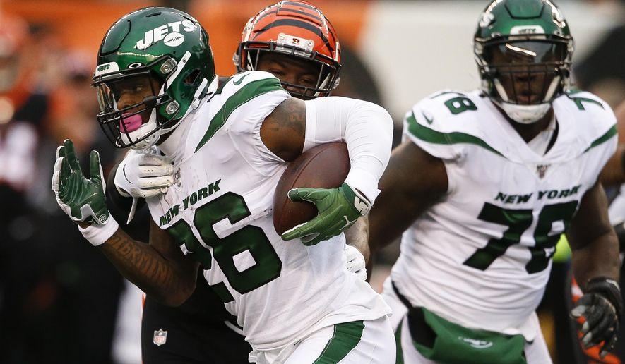 New York Jets running back Le'Veon Bell (26) runs the ball against Cincinnati Bengals linebacker Germaine Pratt, center, during the first half of an NFL football game, Sunday, Dec. 1, 2019, in Cincinnati. (AP Photo/Gary Landers)