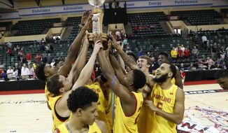 Maryland players celebrate with the Orlando Invitational Trophy after defeating Marquette during an NCAA college basketball game Sunday, Dec. 1, 2019, in Lake Buena Vista, Fla. (AP Photo/Scott Audette)
