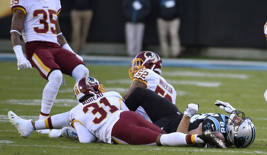 Carolina Panthers tight end Greg Olsen (88) lies on the field following a hit by Washington Redskins linebacker Ryan Anderson (52) while cornerback Fabian Moreau (31) looks on during the second half of an NFL football game in Charlotte, N.C., Sunday, Dec. 1, 2019. (AP Photo/Mike McCarn)